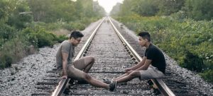 Two friends sitting talking on a railroad track