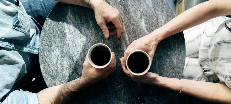 A man and a woman holding coffee cups as they have a conversation or hanging bridge above water