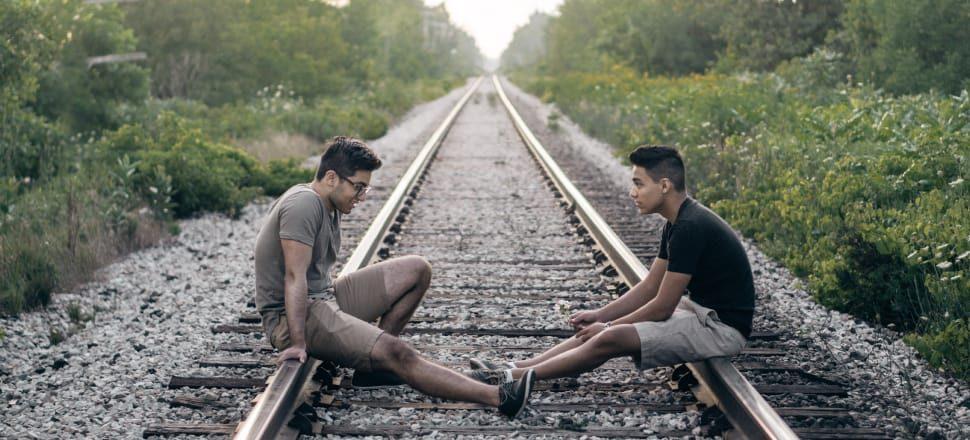 Two friends sitting talking on a railroad track